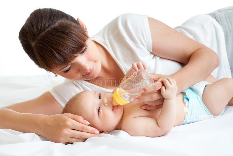 提供她的母亲年轻人的可爱的婴孩 库存图片