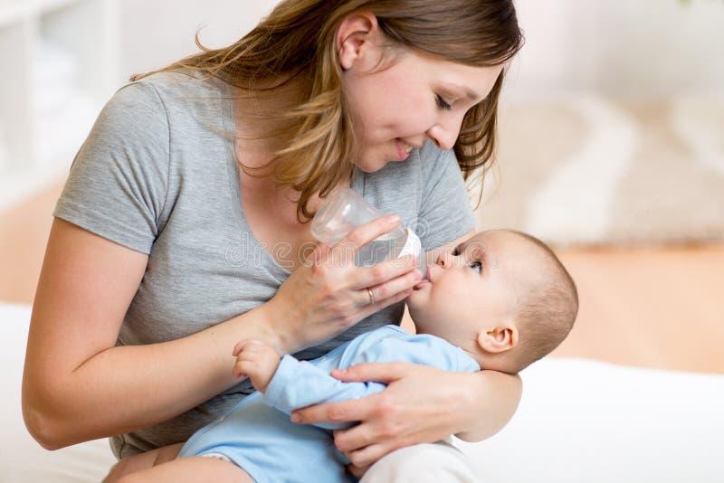 提供她的母亲年轻人的可爱的婴孩 免版税库存照片