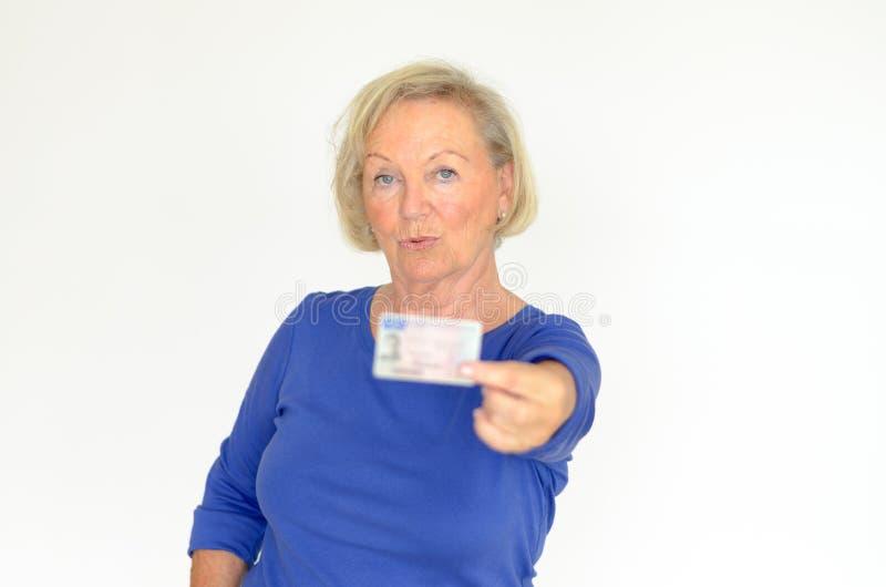 提供她的driverÂ的执照的资深夫人 免版税库存图片