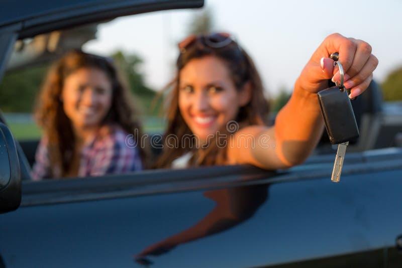 提供援助汽车钥匙的美丽的少妇对照相机,当时 免版税库存照片