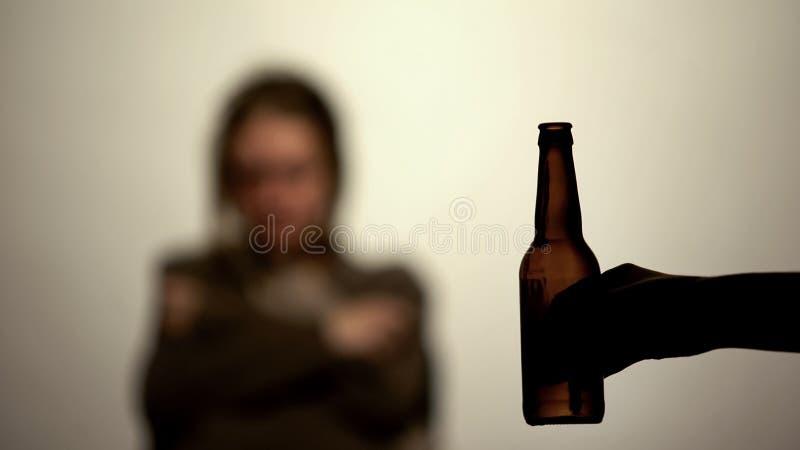 提供的瓶啤酒在手中喝酒精,背景的上瘾的妇女 免版税库存照片
