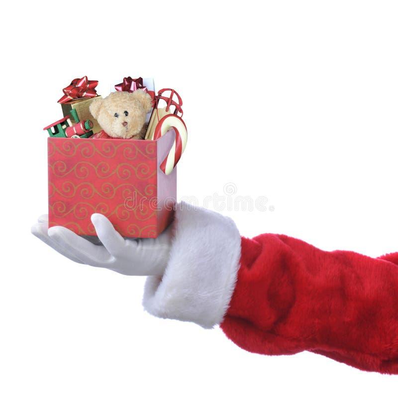 提供礼物盒的圣诞老人手充满玩具和棒棒糖 库存图片