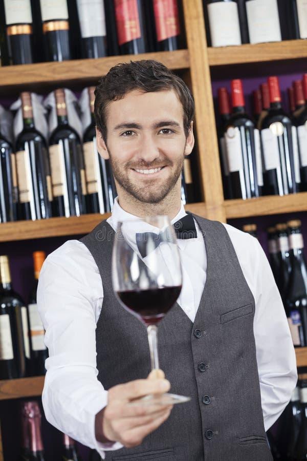 提供红葡萄酒玻璃的侍酒者在酿酒厂 免版税库存照片
