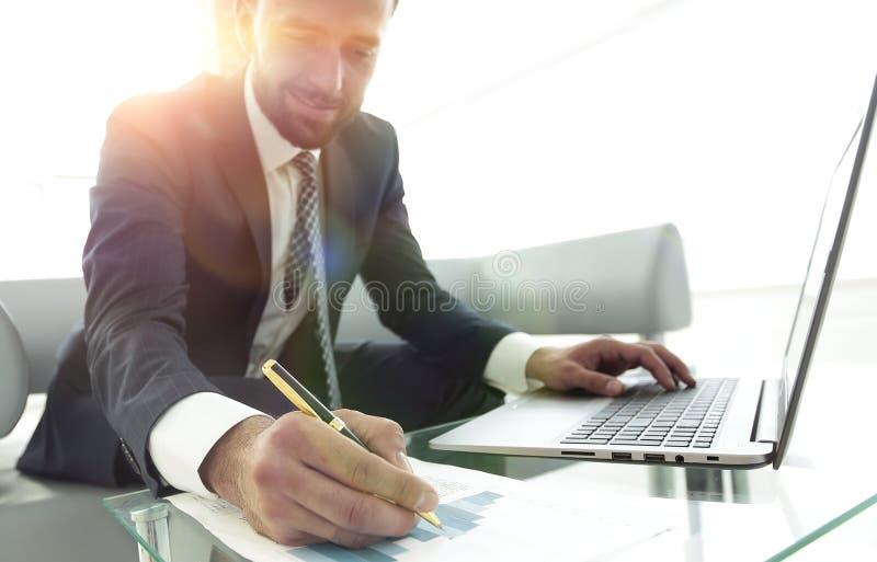 提供经费给经理与在膝上型计算机的商业图表一起使用 库存照片