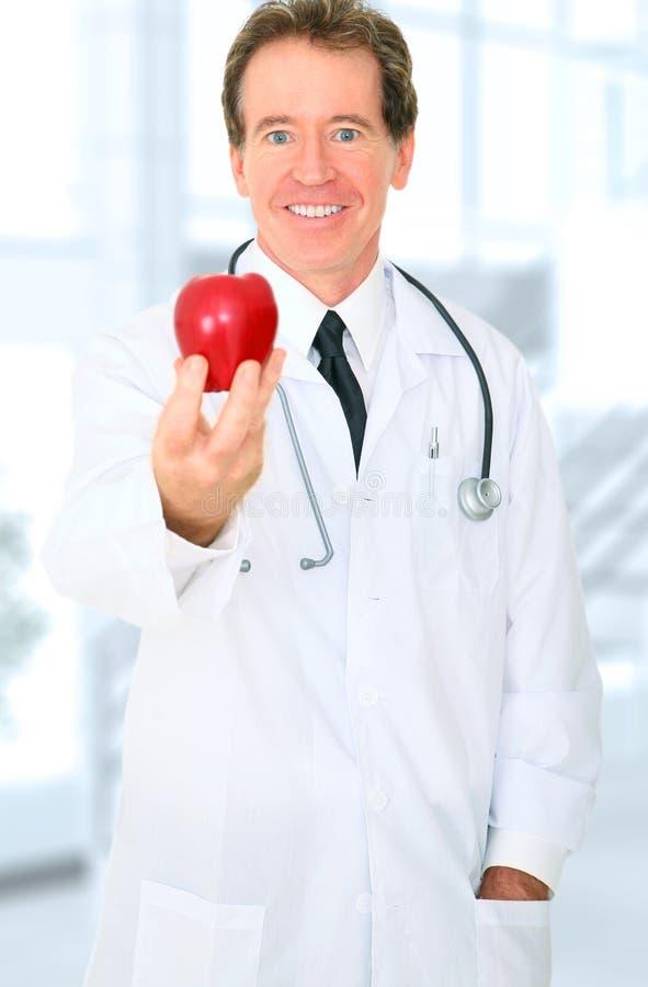 提供耐心的红色前辈的苹果医生 免版税图库摄影