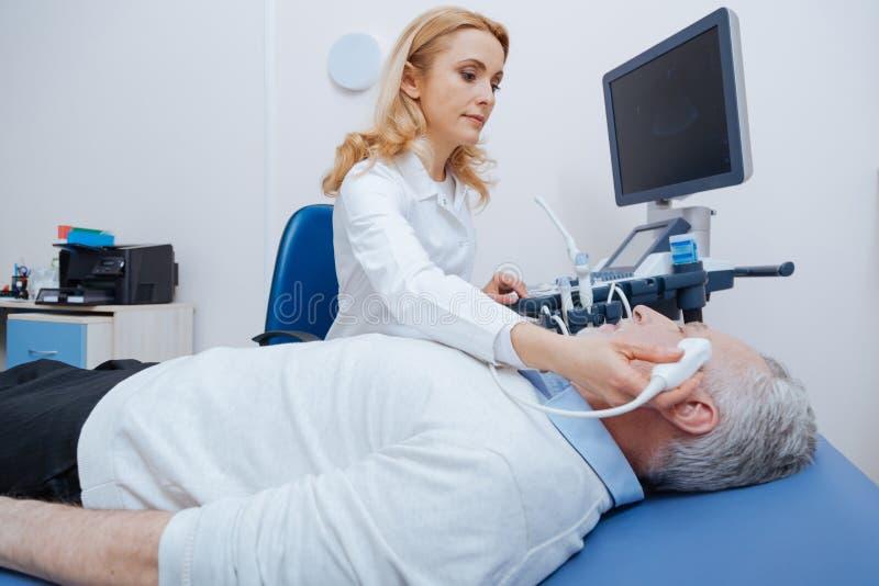 提供脑子超声波的女性sonographer在医院 免版税库存照片