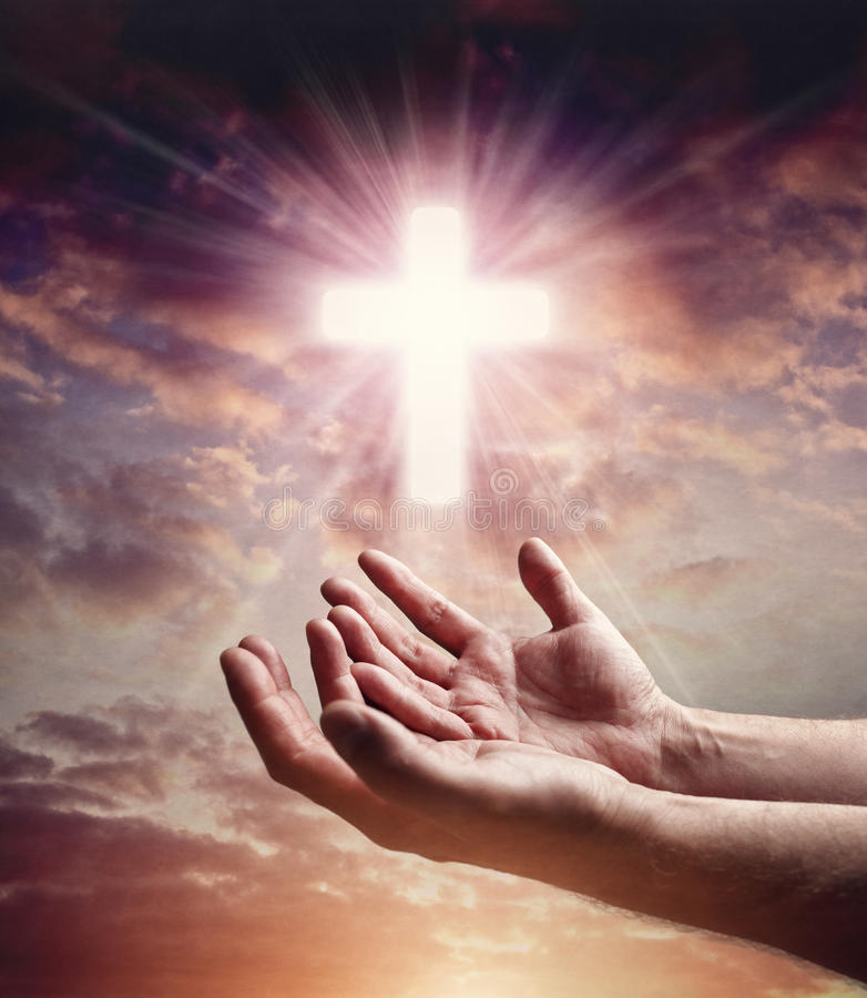 提供援助与在日落天空的耶稣受难象十字架的手 库存图片