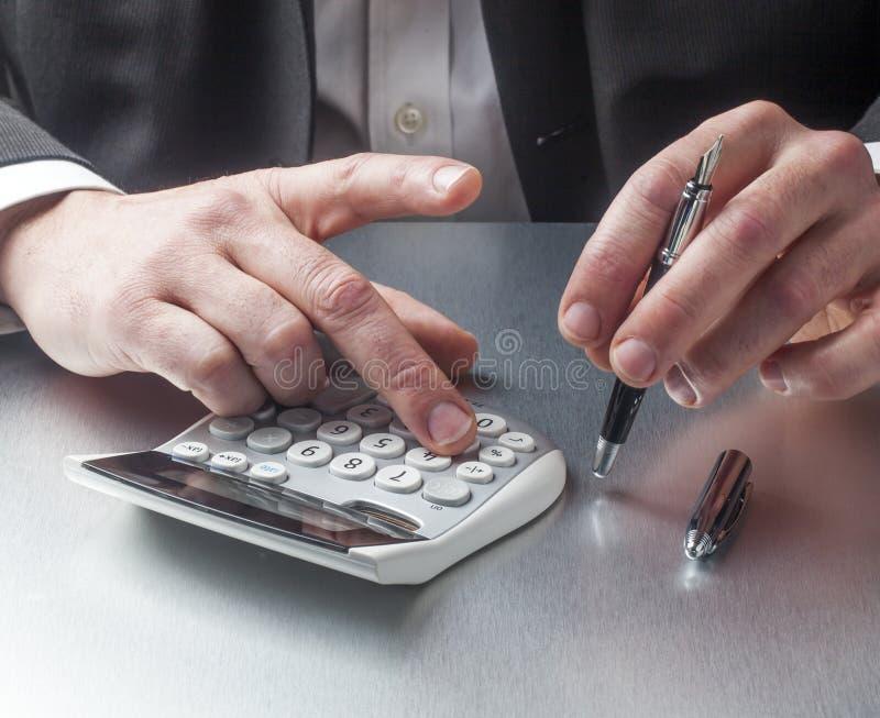 提供经费给有计算器的经理在认为的手上 免版税库存图片