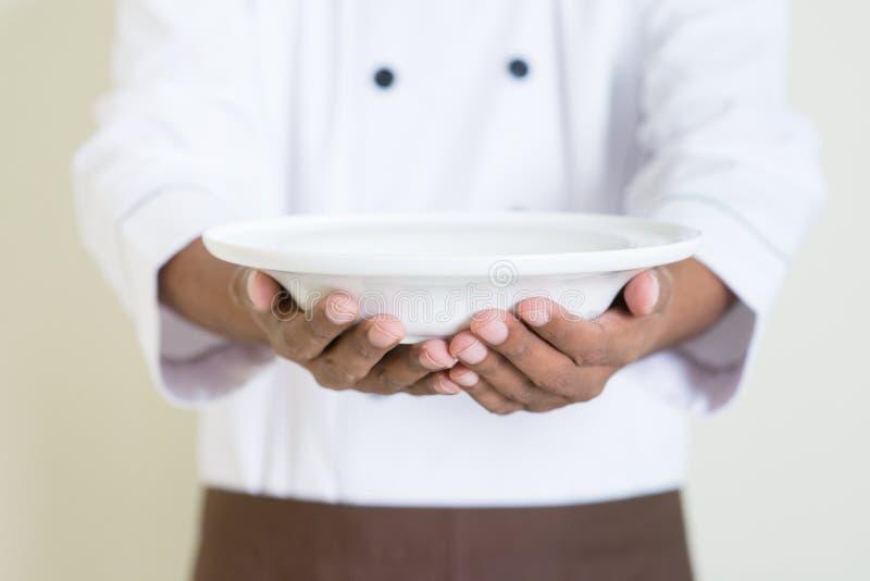 提出一块空的板材的制服的印地安男性厨师 免版税库存图片