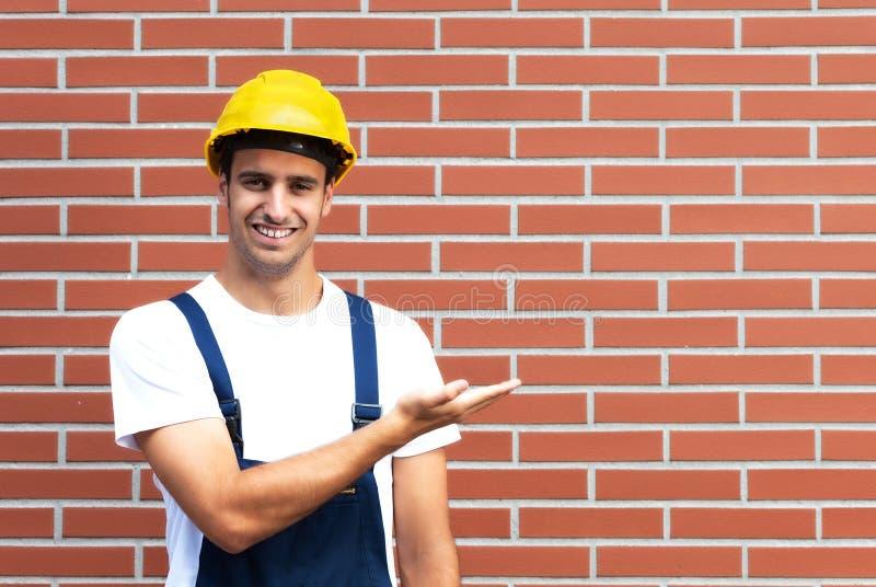 提出在砖墙前面的年轻工人 免版税图库摄影