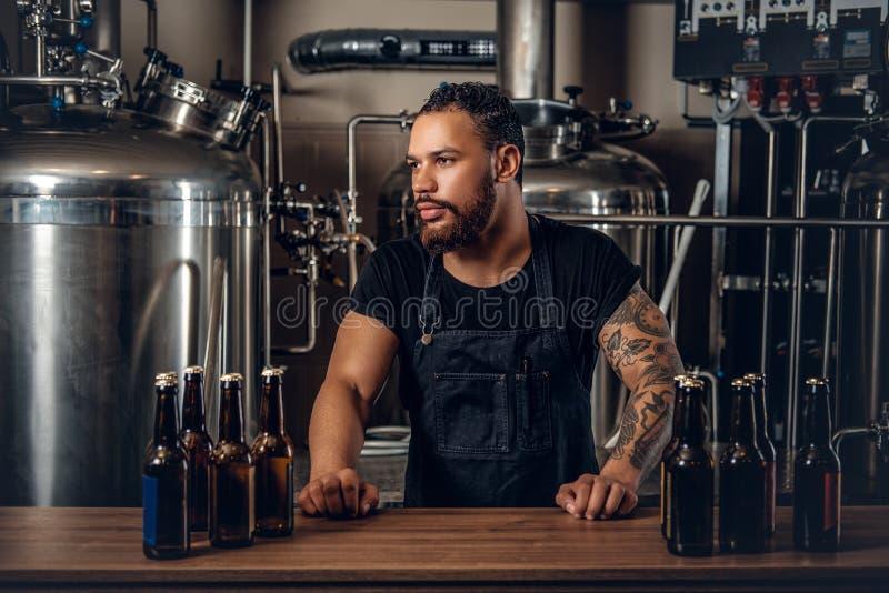 提出工艺啤酒的黑人制造商在microbrewery 免版税库存图片