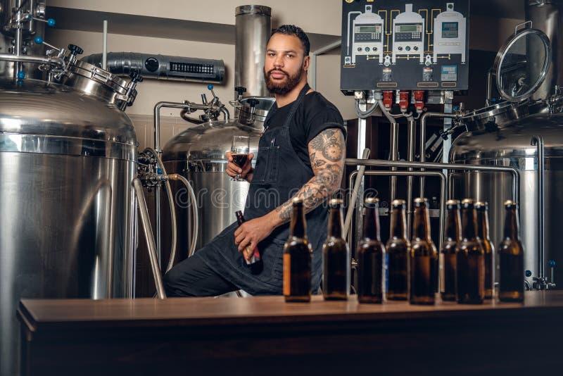 提出工艺啤酒的黑有胡子的maler在microbrewery 库存图片