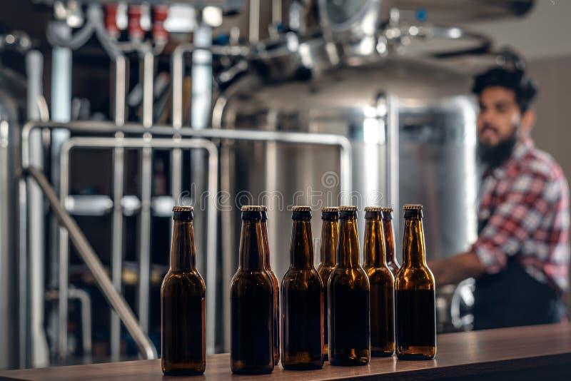 提出工艺啤酒的Indianr男性制造商在microbrewery 库存照片