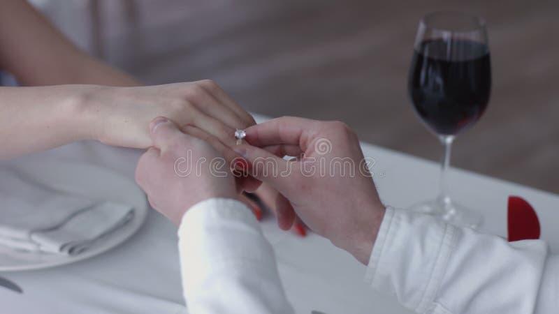 提出提案的愉快的年轻人给定婚戒指他的未婚妻在餐馆,手的关闭 免版税库存图片