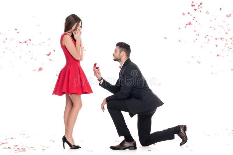 提出男朋友的侧视图女朋友和身分在膝盖 库存照片