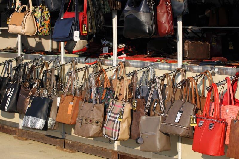 提包和钱包的市场在街道上 品牌袋子的模仿 伪造品被烙记的夫人手 免版税库存图片