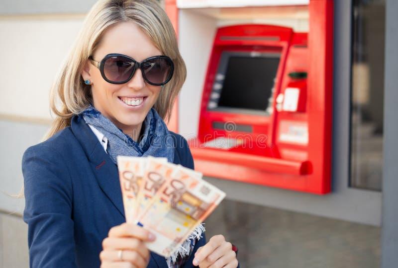 提取妇女的atm货币 免版税图库摄影