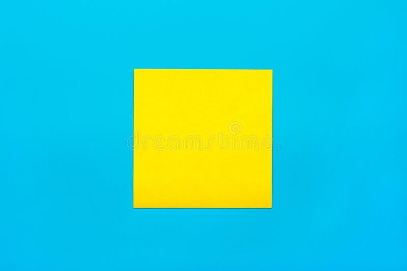 提示和组合一个黄色空的方形的贴纸的概念关闭在与拷贝spase的蓝色背景,假装水平 库存照片