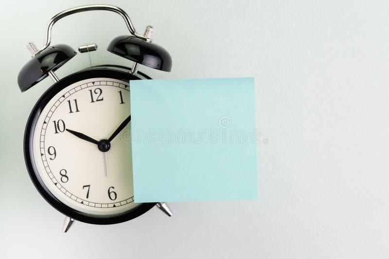 提示,时间,最后期限,停止耽搁或会议日程概念,有空白的稠粘的笔记的闹钟关于文本的上面和 库存照片