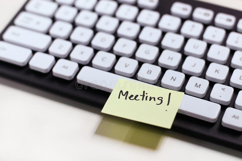 提醒关于键盘的会议的纸笔记 库存图片