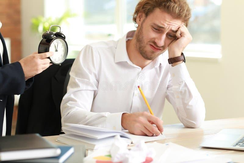 提醒年轻人的上司期间在办公室 免版税图库摄影