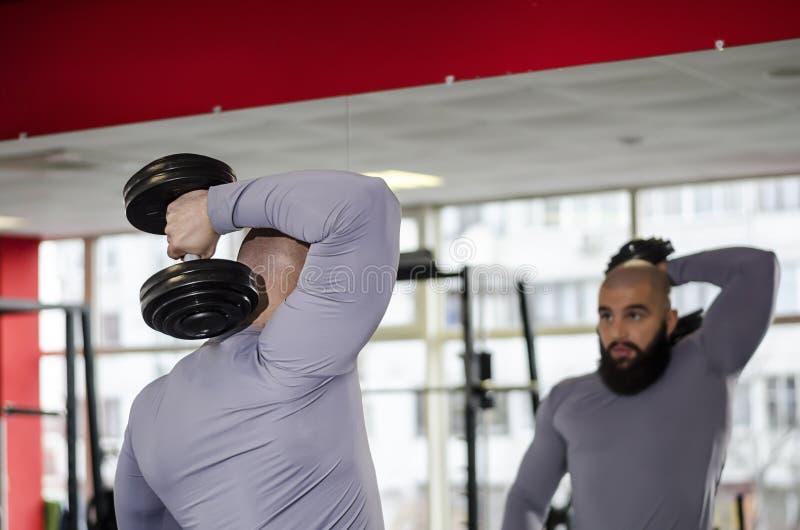 提高哑铃的坚强的男性运动员,看锻炼导致镜子 免版税库存图片