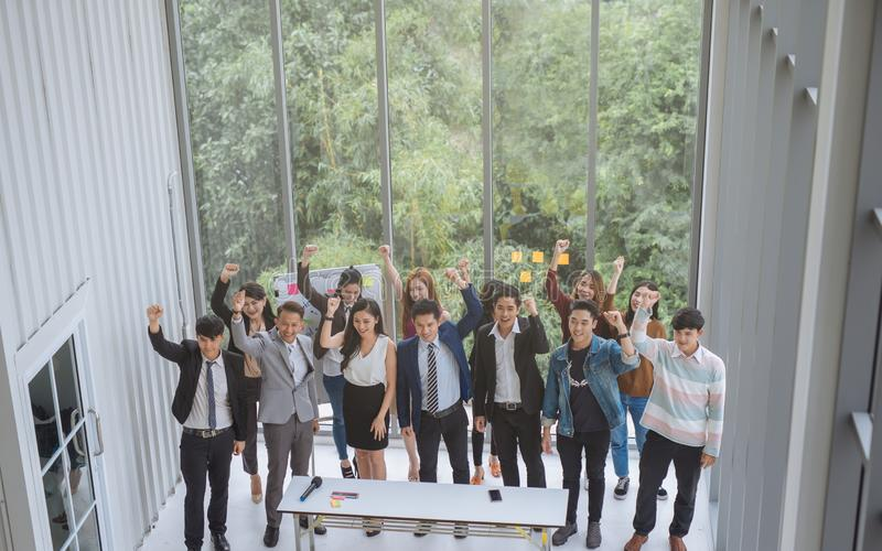 提高胳膊成功成就概念的小组亚洲企业队 图库摄影