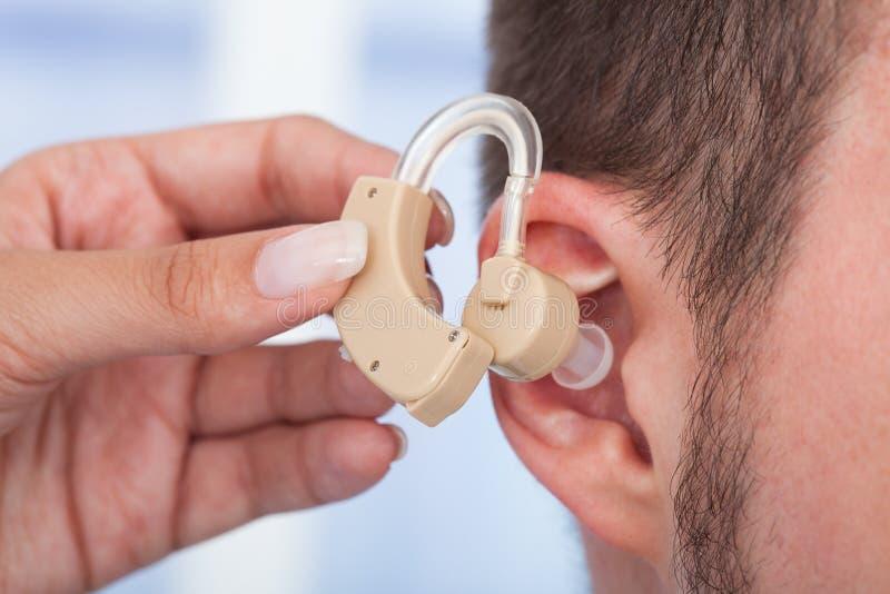 插入助听器的医生在人的耳朵 免版税库存图片