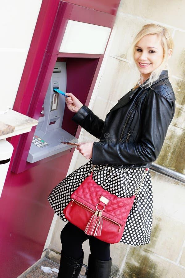 插入卡片的微笑的妇女在ATM 库存照片
