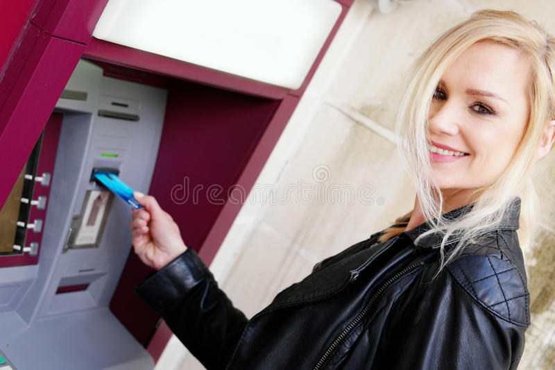 插入卡片的微笑的妇女在ATM 免版税图库摄影
