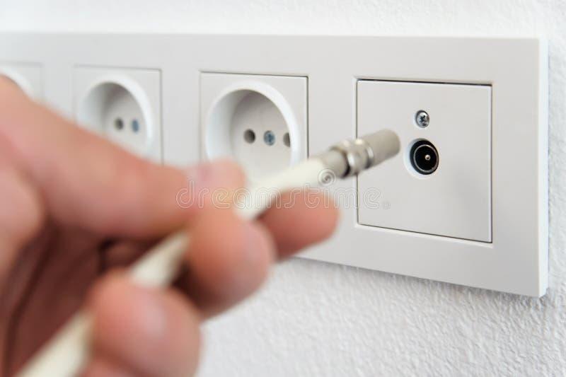 插入天线缆绳对电视出口 库存图片
