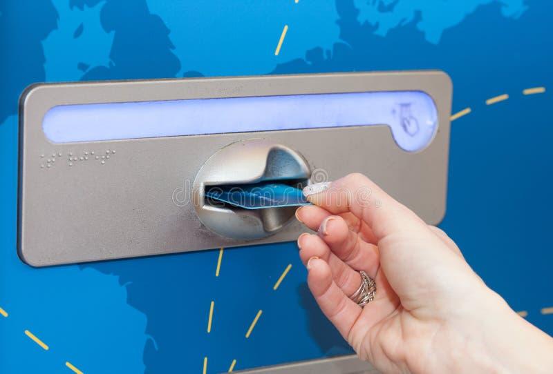 插入她的银行卡的妇女入ATM 免版税库存图片