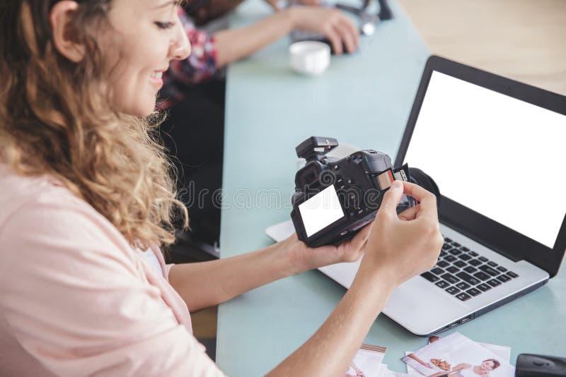 插入存储卡的年轻女性摄影师对camer 免版税库存图片