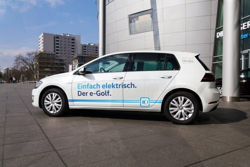 插入式杂种大众e高尔夫球电车坚持在Glaserne Manufaktur -透明工厂前面的充电站 免版税图库摄影