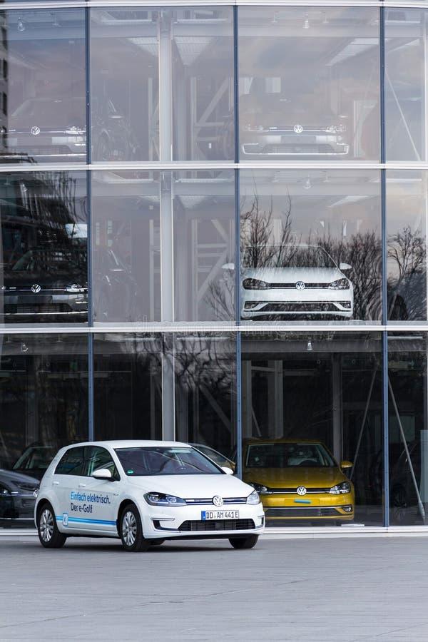 插入式杂种大众e高尔夫球电车坚持在Glaserne Manufaktur -透明工厂前面的充电站 库存图片