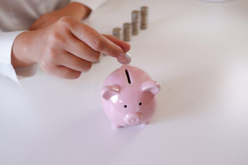 插入硬币的买卖人在有堆的存钱罐中在书桌的硬币 免版税库存图片