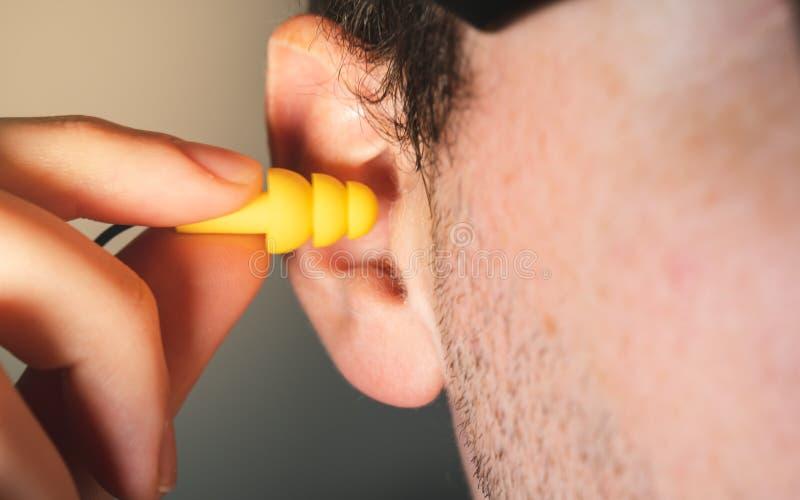 插入黄色听见安全保护耳塞的人工作者在他的看法的耳朵关闭 免版税库存照片