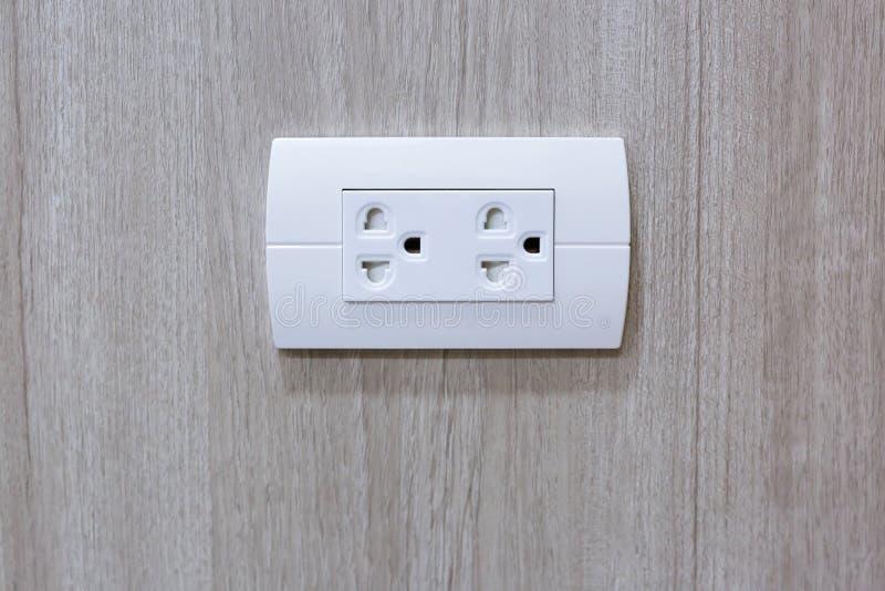 插座到电插口里在木墙壁上的电源输出口 库存照片