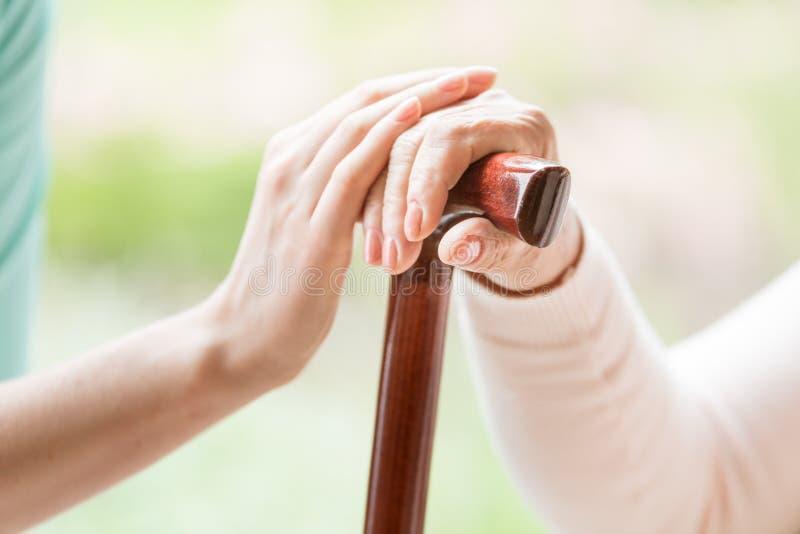 握一个资深人的手的有walki的照料者特写镜头 免版税图库摄影