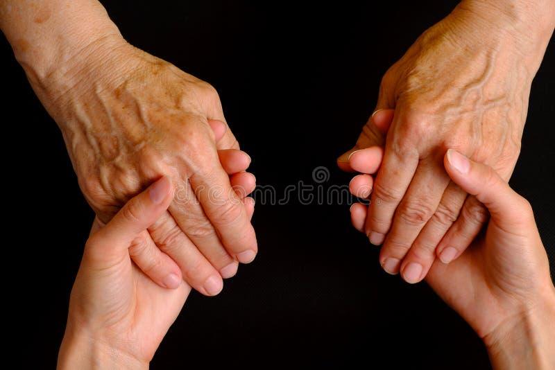 握一名年长妇女的手的少妇的手 库存图片