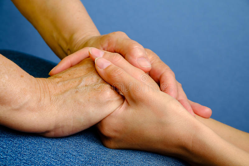 握一名年长妇女的手的少妇的手 图库摄影