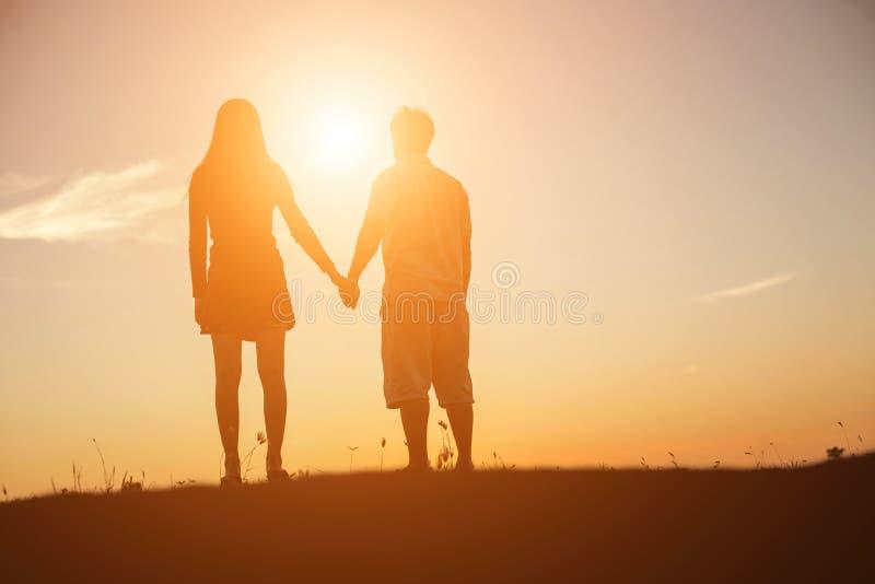 握互相的男人和妇女的剪影手,一起走 免版税库存图片