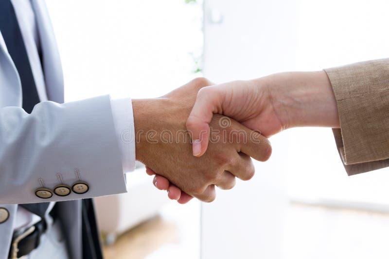 握他们的手的两个商务伙伴在办公室 库存照片