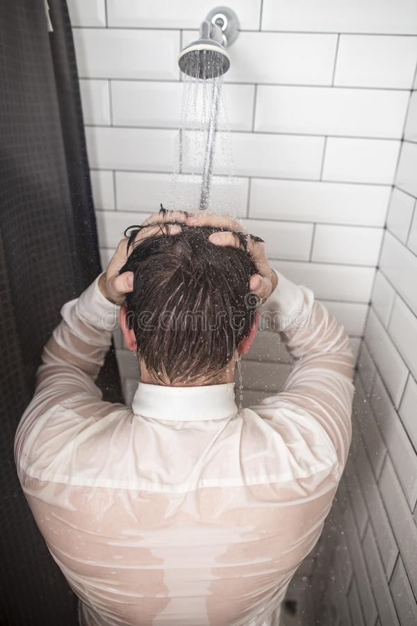 握他的在他的头后的白色衬衫的疲乏的商人手,站立在阵雨在连续温水下以后在a以后 库存图片