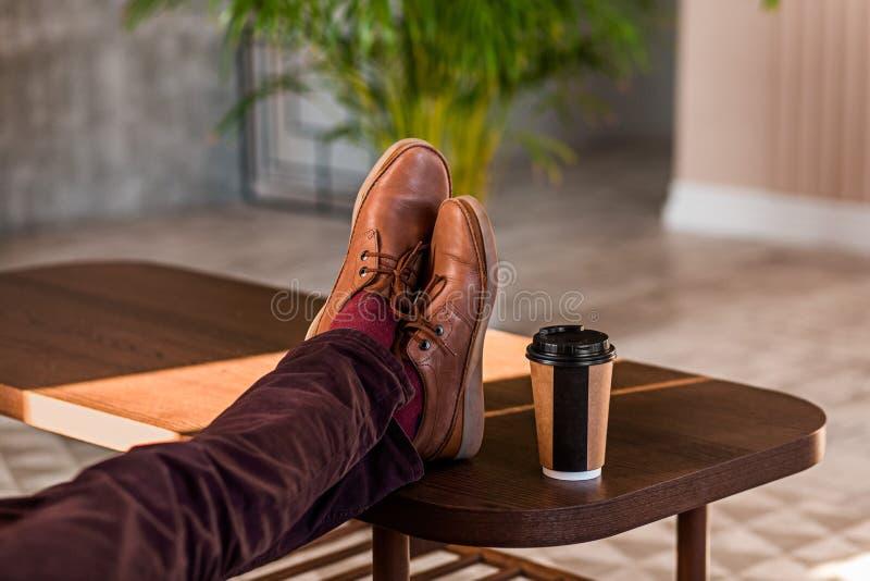 握他的在桌上的一个人的特写镜头腿 免版税图库摄影