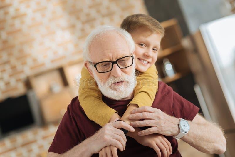握他的孙子手的好年长人 免版税库存图片
