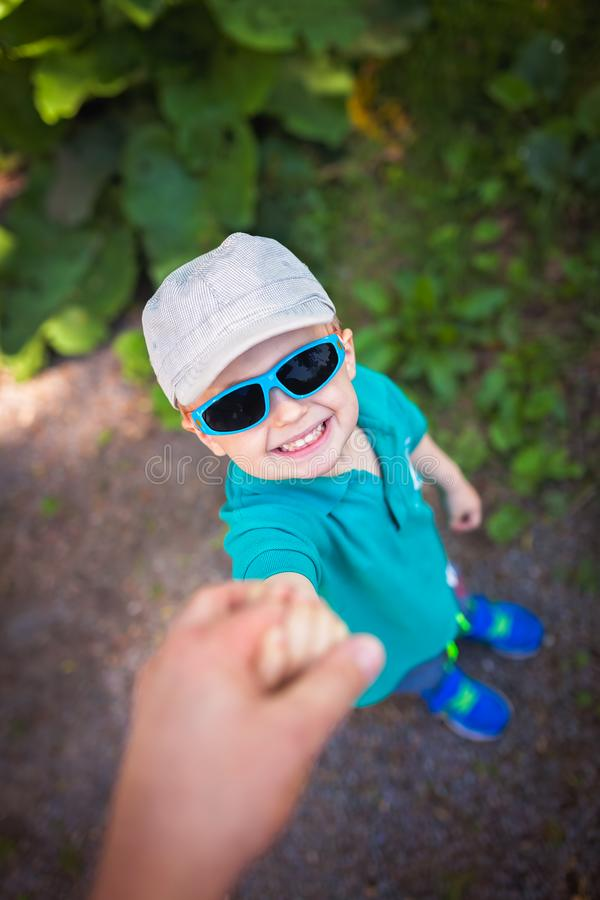 握他的父亲手的愉快的男孩 免版税库存图片
