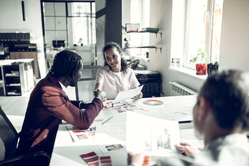 握他的私有助理的手的深色皮肤的室内设计师 图库摄影