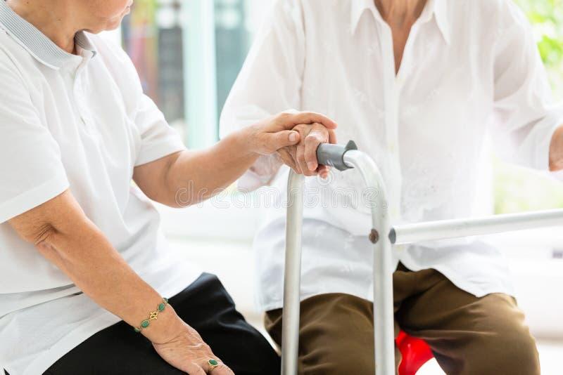 握关心的两个亚裔资深妇女朋友手,一起帮助并且支持她的朋友,时间,有步行者的老人在期间 图库摄影