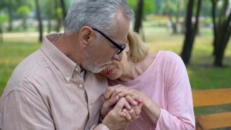 握哀伤的妻子手,健康问题,配偶支持,关心的男性领抚恤金者 免版税库存照片